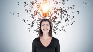 Smiling happy woman in black surrounded by question marks and a glowing light bulb above her head