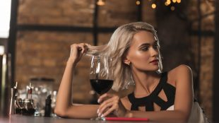 Attractive blonde woman sitting at the bar counter, drinking wine and flirting with someone across the bar