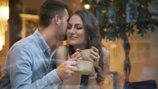 Young couple drinking coffee by cafe window. Man kisses woman's cheek.