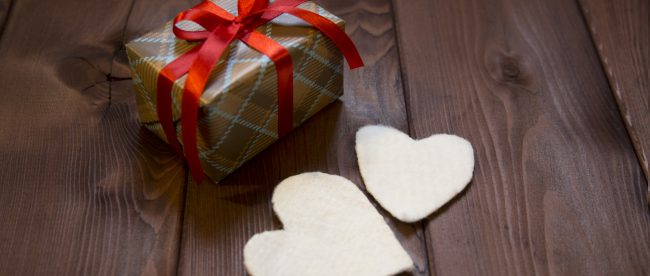 Wrapped holiday gift with golden plaid pattern wrapping and red ribbon, and two white felt hearts sitting beside gift