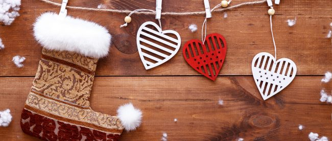 Christmas stocking and white red hearts hanging on brown wooden background with snow