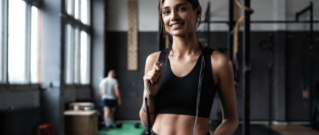 Fit woman standing in gym with skipping rope over her shoulders