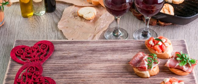 Wooden serving tray with appetizers and decorative hearts, alongside two glasses of red wine ready for a romantic date night