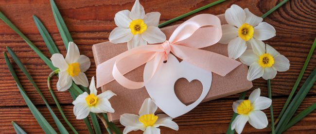 Daffodil flowers and a brown gift package with a heart-shaped tag arranged on a wooden table