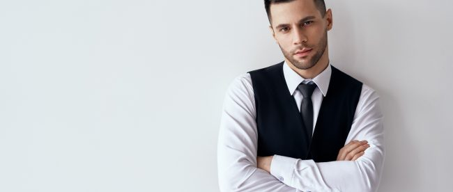 Handsome confident man in elegant suit with crossed arms on white background