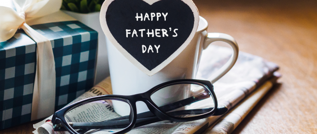 Father's Day scene with a mug and reading glasses sitting on a folded-up newspaper next to a nicely wrapped gift
