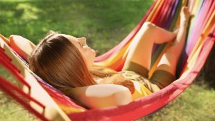 A young woman relaxes peacefully in a backyard hammock on a sunny summer day.
