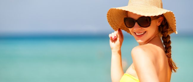 Pretty woman in a sun hat and sunglasses on a hot sumer day, smiling at the camera with the ocean in the background