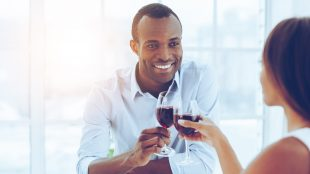 Smiling man enjoying a romantic dinner with his wife, sitting at the dinner table and toasting with wine glasses