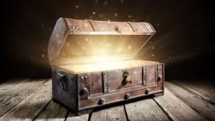 A vintage wooden treasure chest opens to reveal a glowing interior and sparkles