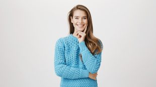 Woman with long brown hair wearing a light blue sweater smiles at the camera. She is touching her chin and face in a thinking posture.