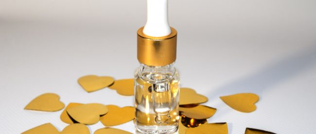 A small eyedropper bottle full of clear liquid. It is surrounded by pieces of small gold heart-shaped confetti.
