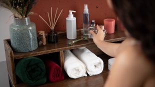 Woman replaces a bottle of fragrance on a bathroom shelf, next to incense and bath towels.