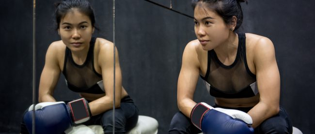 Young female boxer sitting next to a mirror, giving the camera a confident smile.