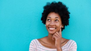 Happy young African American woman smiling and thinking about something, touching her fingertip to her cheek, with a bright blue background..