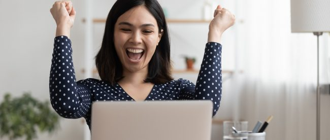 Woman sitting at her laptop, raising her fists and cheering happily while she looks at the laptop screen.