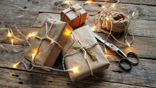 Small wrapped gift packages on a wooden table. A string of white lights is draped across the packages. A roll of twine and pair of scissors sit next to the packages.