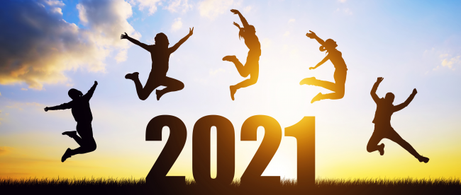 Silhouettes of happy people leaping over the number 2021