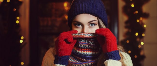 Pretty young woman bundled up for winter, with a knitted cap, scarf over her face, and gloves.