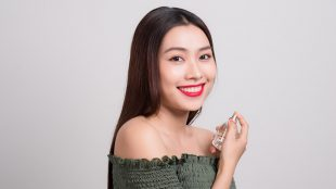 Smiling young Asian woman holding a perfume bottle