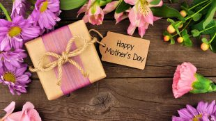 """Fresh flowers and a Mothers Day gift box with tag that reads """"Happy Mother's Day"""" sitting on a rustic wooden surface"""
