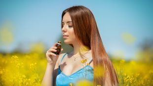 Youmg brown-haired woman in a blue tank top, standing in the sunshine in a field of yellow flowers that come up to her waist, smelling a brown dripper bottle of liquid.