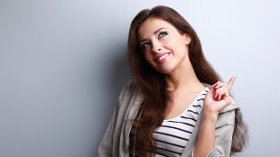 Young woman holding up one finger and looking upwards in a thoughtful way, with a smile on her face