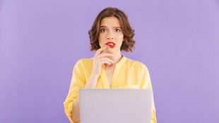 Woman holding up her laptop and biting her lip with a confused expression on her face.