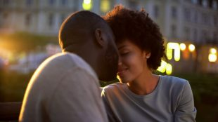 Black couple leaning close for a kiss on an evening date