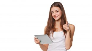 Young woman in white tank top looking up from her tablet and giving a thumbs up sign