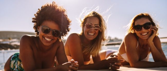 Three female friends lying on their stomachs on the deck of a boat on a sunny summer day, smiling happily at the camera