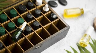 A wooden box with individual compartments for glass bottles, including dripper bottles and eyedropper bottles, holding DIY fragrances