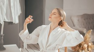 Woman in bathrobe sitting at her bedroom table, leaning back in her chair with her eyes closed, spraying pheromone perfume out of a glass square bottle