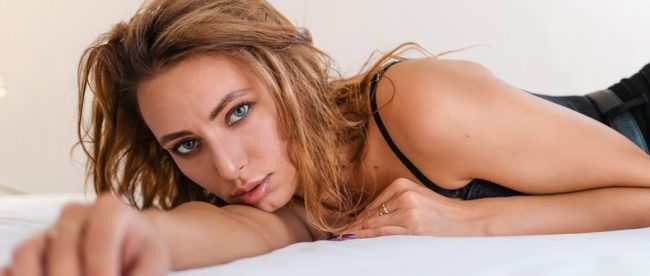 Woman with messy light brown hair and wearing a black tank top lies on her stomach in bed, staring into the camera