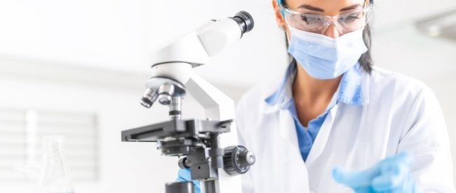 Lab worker in a lab coat and surgical mask sitting at her microscope, looking at a microscope slide before putting it on the microscope
