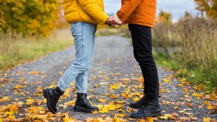 Two people in fall coats hold hands while standing face to face on a road covered in fallen autumn leaves. You cannot see their faces.