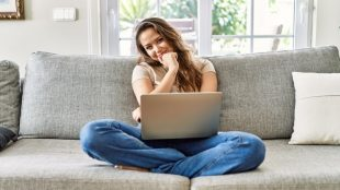 Happy young woman sitting cross legged on her couch with her laptop in her lap. Her head is tilted to one side and her hand is against her chin in a thinking pose.
