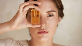 Pretty woman holding an eyedropper bottle full of golden oil up in front of one eye