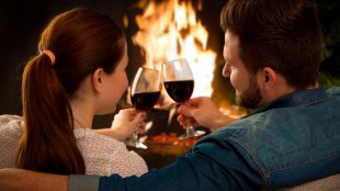 A couple with their backs to the camera cuddle up on their sofa and clink together two wine glasses in front of a fire in their fireplace